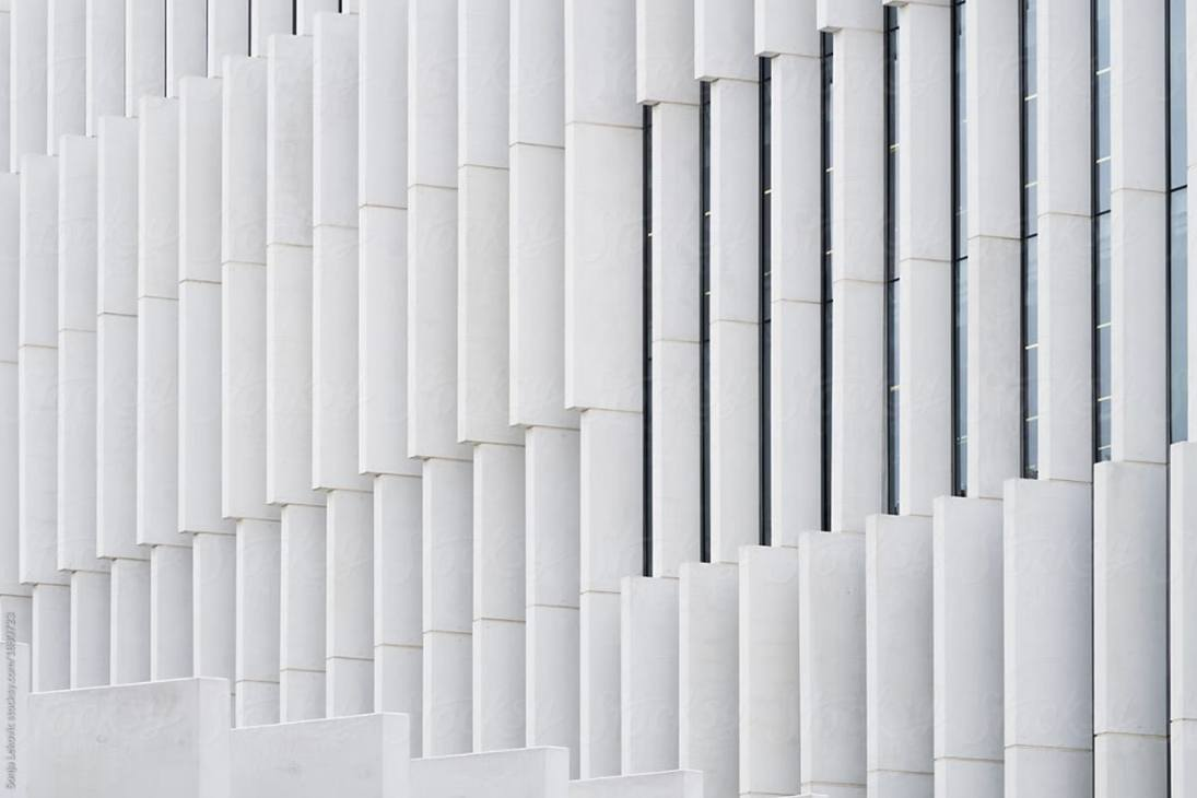 The outside view of a white wall of a building with many small columns that look like pvc pipes.
