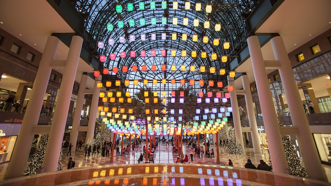 Multi colored display above a water feature, inside a high end shopping plaza on two levels.