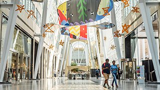 Interior view of a shopping mall. The mall is decorated with gold stars and assorted flags.