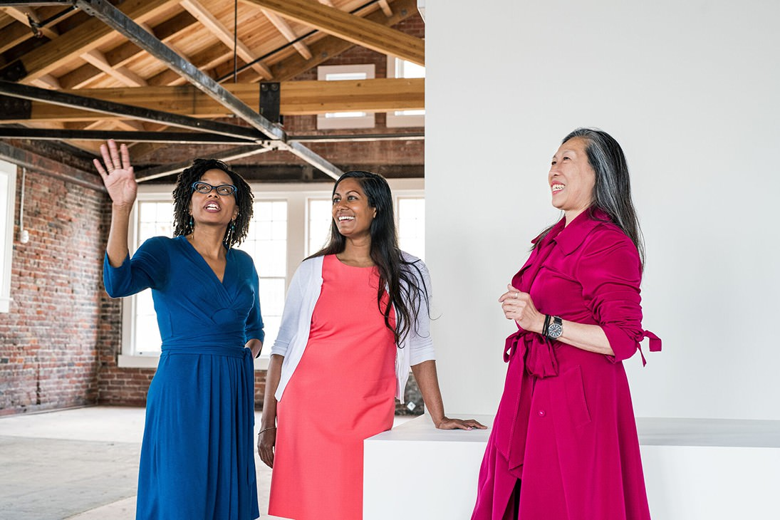 Three women in different color dresses look around an empty room. The room looks to be just built.