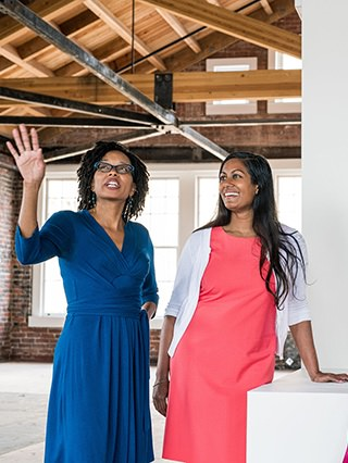 Two women are looking up and discussing something in what looks like a loft. One is wearing blue, the other is in red.