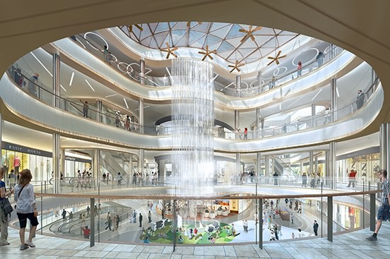 A floor to ceiling water feature is seen in a busy indoor multilevel shopping mall.