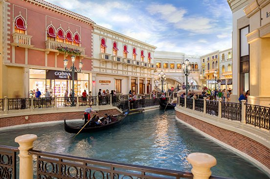 Buildings surrounding a body of water where you can ride a gondola has many buildings in a pink and off white color.
