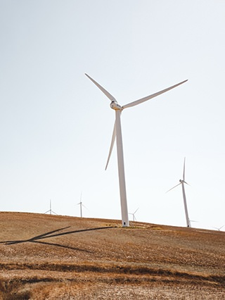 Several white colored wind turbines can be seen operating in a very large, brown field.