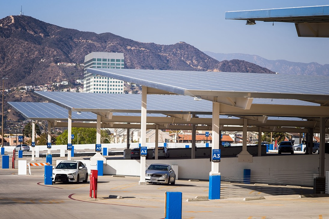 Two cars parked in a parking garage with solar panel roof and a large mountain in the background.